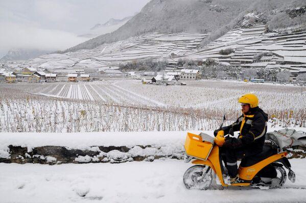Поштар на мотоциклу вози кроз свежи снег у Ејглу, кантон Вауд у западној Швајцарској, 24. новембра 2008. године. - Sputnik Србија