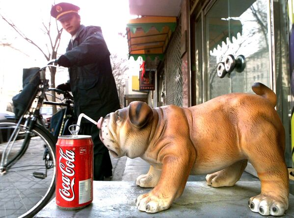 Кинески поштански радник одлази са својим бициклом након што је 16. фебруара 2000. године у Пекингу допремио пошту у модни салон испред ког је статуа порцуланског пса. - Sputnik Србија