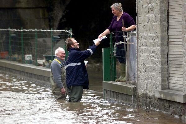 Поштар који ради упркос поплавама у селу близу Лијежа, 28. јануара 2002, након што су обилне кише проузроковале поплаве у многим областима Белгије. - Sputnik Србија