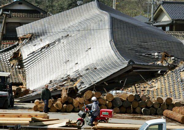 Поштар на мотоциклу поред срушених зграда на Вајима, једном од подручја која су најтеже погођена у префектури Ишикава (држава), северни Јапан, 26. март 2007. - Sputnik Србија