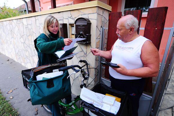 Радница Мађарске поштарска компаније Бернадет Каса доставља писмо човеку округа у Будимпешти, 18. октобра 2013. - Sputnik Србија