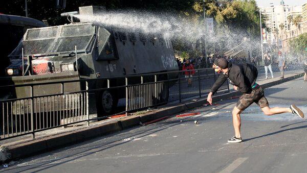 Demonstrant baca kamenice na pripadnike policije na protestu u Čileu - Sputnik Srbija