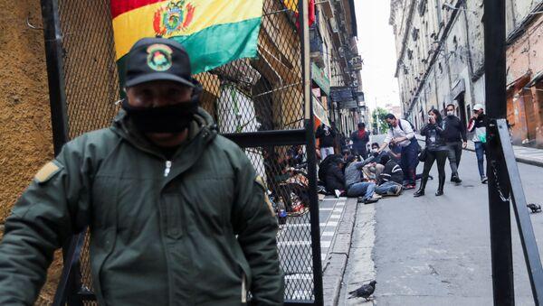 Припадник снага безбедности Боливије стоји поред присталица опозиције током сукоба на протесту у Ла Пазу - Sputnik Србија