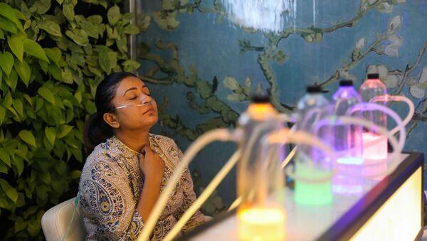 Жена удише кисеоник помешан са ароматерапијом у бару са кисеоником у Њу Делхију - Sputnik Србија