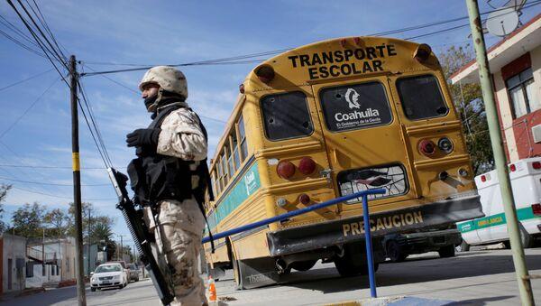 Војни полицајац испред изрешетаног школског аутобуса после сукоба са нарко-картелом на северу Мексика. - Sputnik Србија