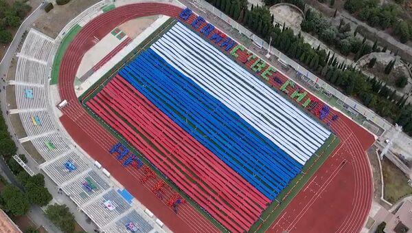 Deca iz najećeg dečijeg centra na svetu razvila na Krimu džinovsku zastavu Rusije  - Sputnik Srbija