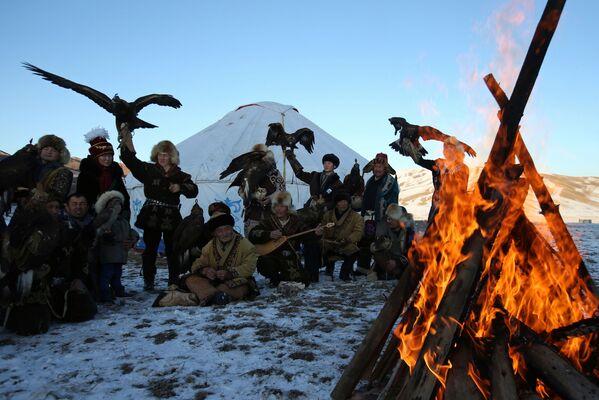 Lovci sa pripitomljenim zlatnim orlovima i sokolima okupljaju se oko vatre tokom tradicionalnog lovačkog takmičenja - Sputnik Srbija