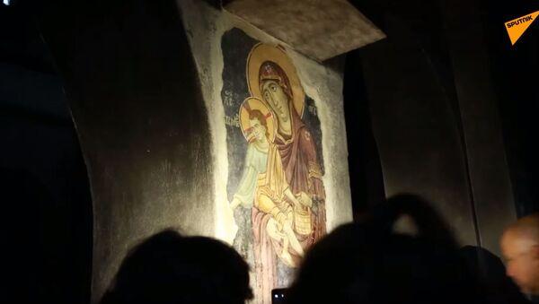 Лице Богородице и других светитеља током вечерње молитве верници и туристи откривају светлима моблиних телефона. - Sputnik Србија