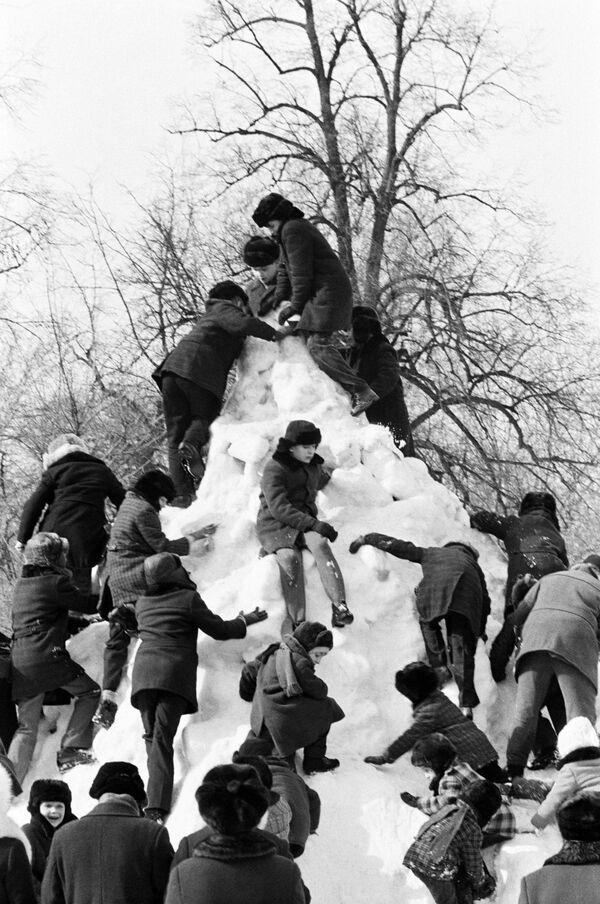 Деца се пењу на снежни тобоган током распуста, 1979. - Sputnik Србија