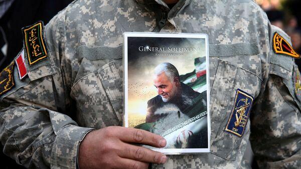 Демонстрант носи фотографију генерала Касема Сулејманија на протесту против његовог убиства у Техерану - Sputnik Србија