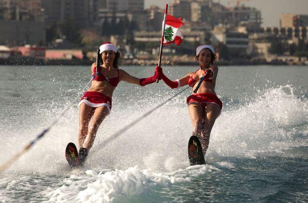 U nedostatku snega, može i skijanje na vodi. Libanke u kostimu Deda Mraza - Sputnik Srbija