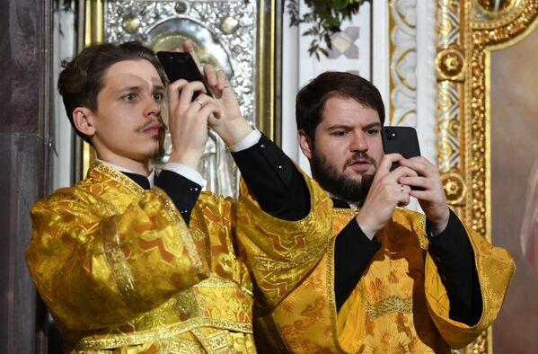 Pravoslavni sveštenici slikaju tokom božićne liturgije u Hramu Hrista Spasitelja u Moskvi - Sputnik Srbija