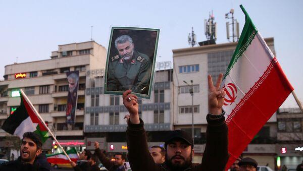 Човек држи фотографију убијеног иранског генерала Касема Сулејманија током славља због напада Ирана на америчке војне базе у Ирану - Sputnik Србија