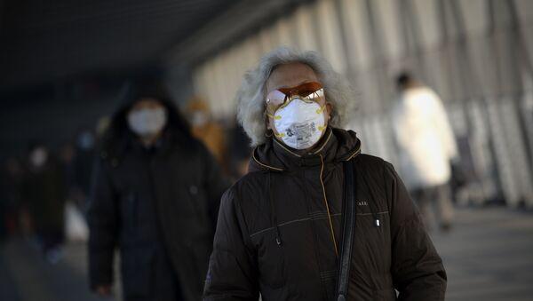 Човек носи маску због великог загађења ваздуха у Пекингу - Sputnik Србија