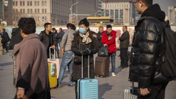 Путници снимљени на железничкој станици у Пекингу са заштитним маскама - Sputnik Србија