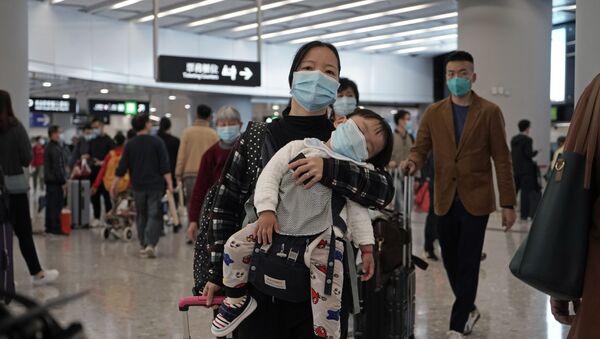 Путници носе заштитне маске за лице на улазу железничке станице у Хонгконгу - Sputnik Србија