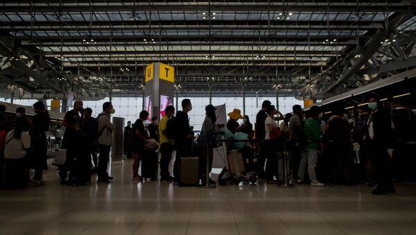 Туристи са маскама чекају у реду на аеродрому - Sputnik Србија