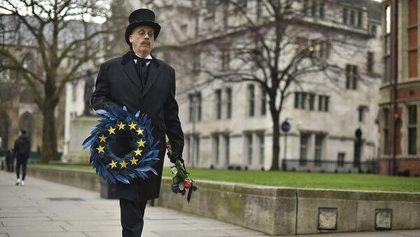 Човек обучен као гробар носи венац за заставом Европске уније у Лондону уочи брегзита. - Sputnik Србија