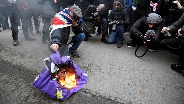 Човек пали заставу Европске уније на Дан Брегзита у Лондону - Sputnik Србија