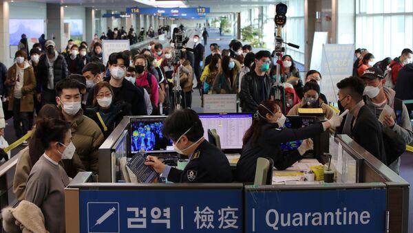 Путници из Кине са маскама на лицу пролазе контролу на аеродрому - Sputnik Србија