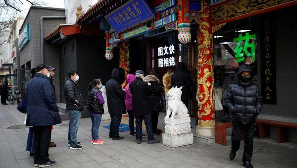 Ljudi čekaju u redu ispred apoteke u Pekingu da kupe maske - Sputnik Srbija