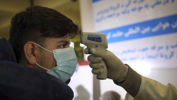 Медицински радник проверава телесну температуру путнику на међународном аеродрому у Кабулу у Авганистану - Sputnik Србија