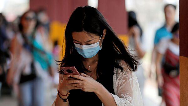 Devojka sa maskom na licu gleda u mobilni telefon - Sputnik Srbija