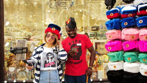 Turisti se slikaju ispred izloga GUM-a u Moskvi. - Sputnik Srbija