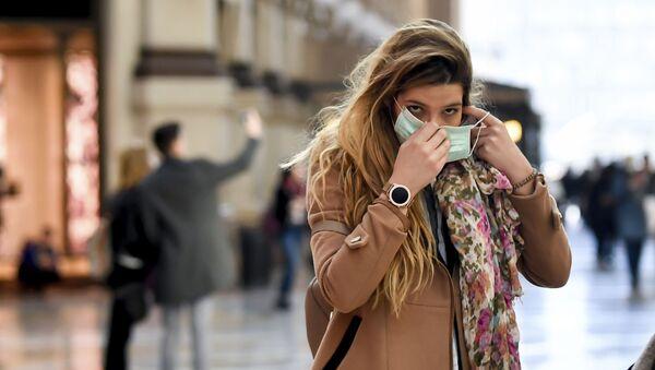 Žena u Italiji stavlja zaštitnu masku na lice - Sputnik Srbija