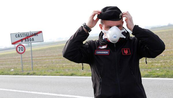 Италијански полицајац носи маску током патроле у граду Кастиљоне Д'Ада - Sputnik Србија