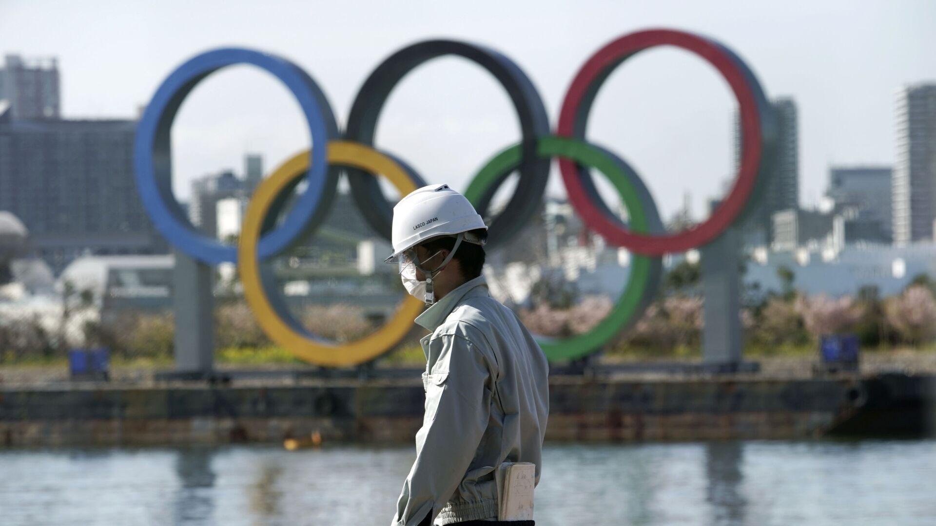 Човек с маском испред олимпијских кругова у Токију. - Sputnik Србија, 1920, 09.03.2021
