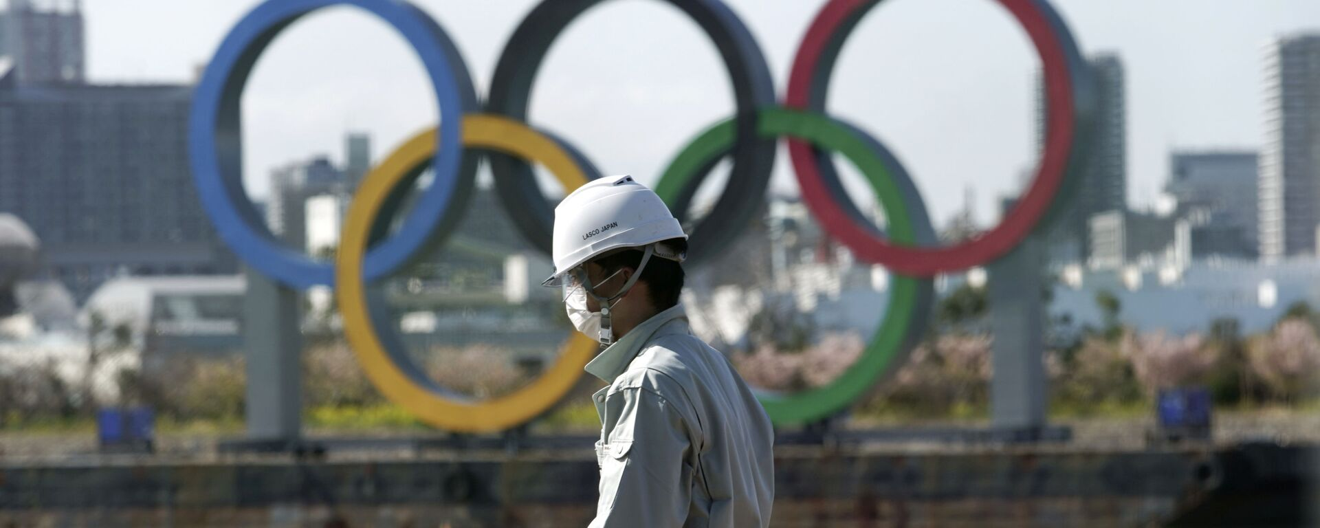 Čovek s maskom ispred olimpijskih krugova u Tokiju. - Sputnik Srbija, 1920, 23.07.2021