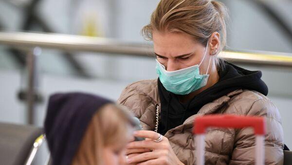 Žena nosi masku zbog koronavirusa - Sputnik Srbija