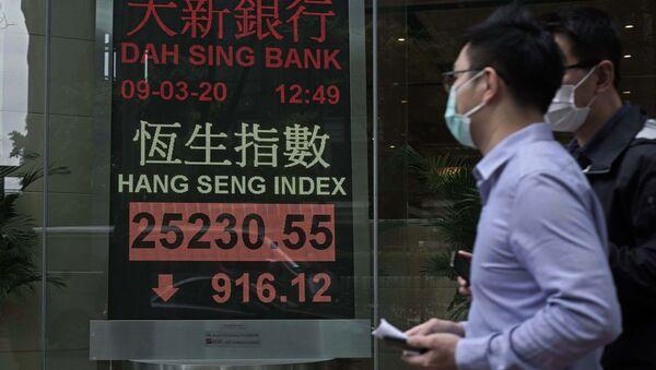Čovek sa maskom prolazi pored berzanskog displeja ispred banke u Hongkongu - Sputnik Srbija