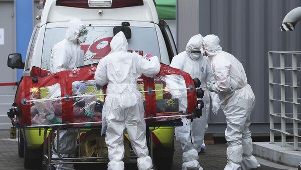 Медицинари у заштитној униформи премештају пацијента из амбулантних кола у болницу у Сеулу - Sputnik Србија