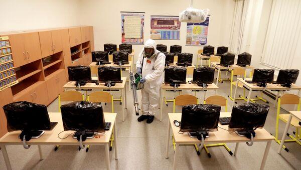 Radnik u zaštitnom odelu dezinfikuje učionicu u osnovnoj školi zbog problema sa koronavirusom u Pragu - Sputnik Srbija