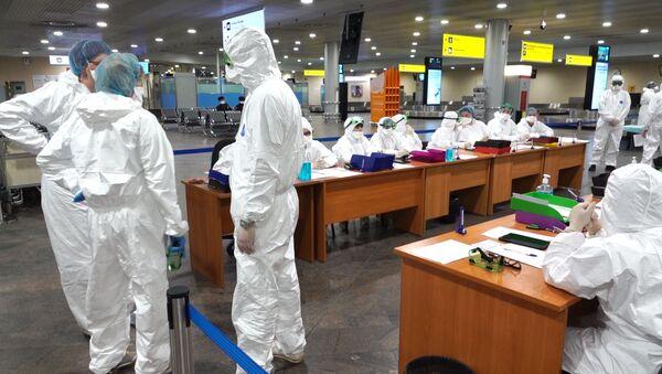 Медицински радници у заштитним оделима на аеродрому Шереметјево у Москви - Sputnik Србија