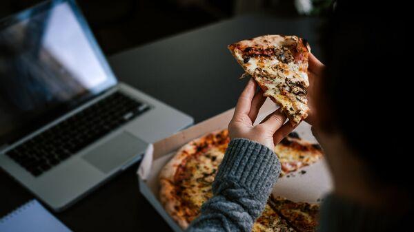 Човек једе пицу док ради за лаптопом - Sputnik Србија