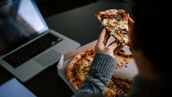 Čovek jede picu dok radi za laptopom - Sputnik Srbija