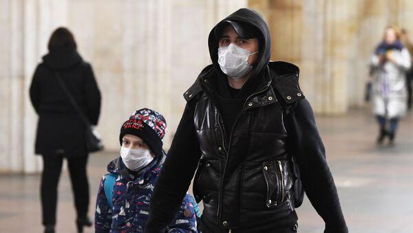 Мушкарац са маском и дететом у метроу у Москви - Sputnik Србија