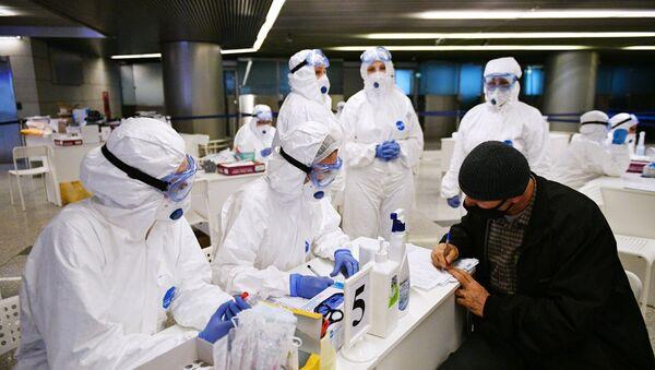 Medicinski radnici proveravaju zdravstveno stanje putnika na aerodromu Vnukovo u Moskvi - Sputnik Srbija