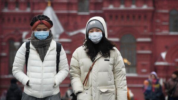 Иностранные туристы в защитных масках на Красной площади в Москве - Sputnik Србија