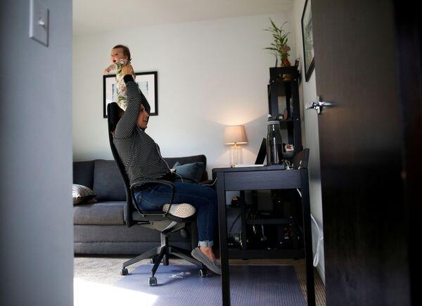 Чланица градског већа из Сијетла Тереза Москеда са својом ћерком док обавља конференцијски састанак телефонском везом. - Sputnik Србија