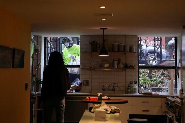 Њујорчанка Наоми Хасбрук преузима храну од достављача док ради од куће. - Sputnik Србија