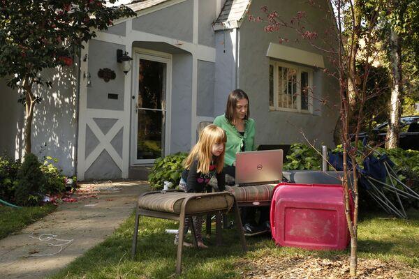 Алисон Стефенсен и њена ћерка Елин (3), док ради у канцеларији коју је поставила у предњем дворишту свог дома у Сакраменту, Калифорнија. - Sputnik Србија