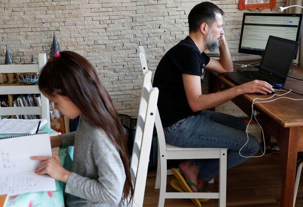 ИТ стручњак из Будимпеште Чаба Пошта ради у свом стану док његова ћерка поред ради домаће задатке. - Sputnik Србија
