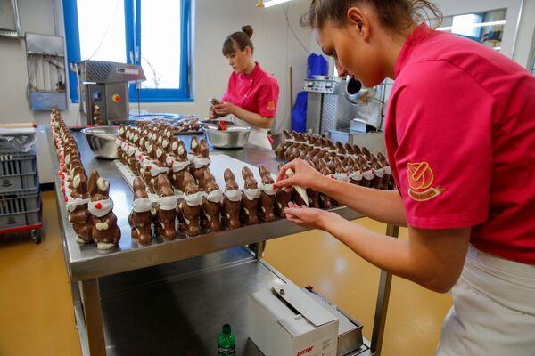 Припрема чоколадних ускршњих зека са заштитном маском у посластичарници у Швајцарској. - Sputnik Србија