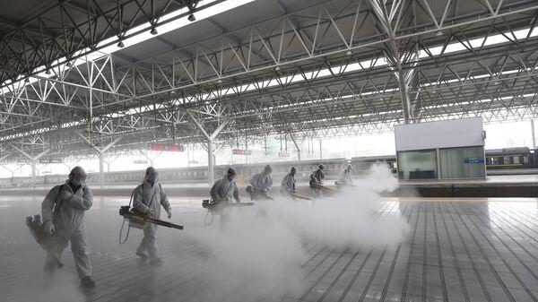 Radnici u zaštitnim odelima dezinfikuju platformu železničke stanice u Jičangu u kineskoj provinciji Hubej. Kina je ponovo otvorila neke železničke i autobuske stanice nakon ukidanja karantina u provinciji Hubej - Sputnik Srbija