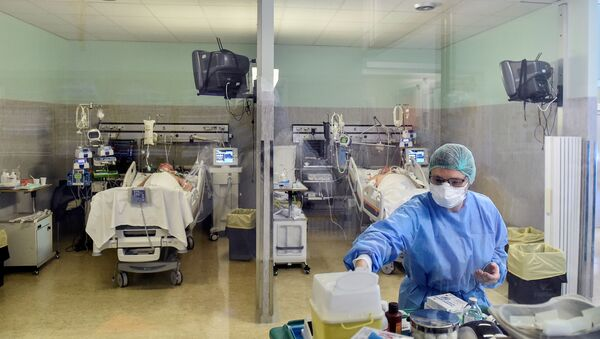 Лекар у заштитном оделу поред пацијената са вирусом корона КОВИД-19 у болници у Италији - Sputnik Србија