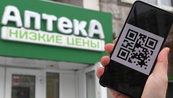 Čovek drži telefon sa kju-ar kodom. - Sputnik Srbija